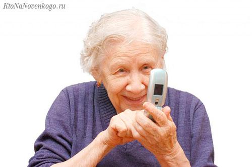 Бабушка смотрит в устаревший сотовый телефон