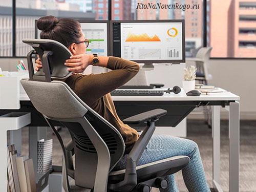 Женщина сидит в эргономичном кресле и получает от этого удовольствие
