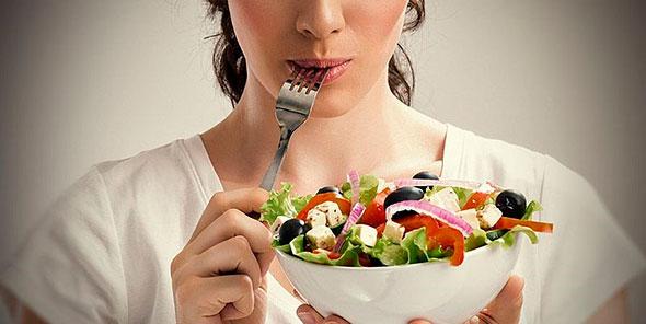Женщина держит миску с витаминным салатом