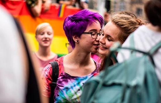 Девушка целует другую девушку в щеку