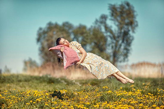 Девушка висит над полем лежа головой на подушке (спит)