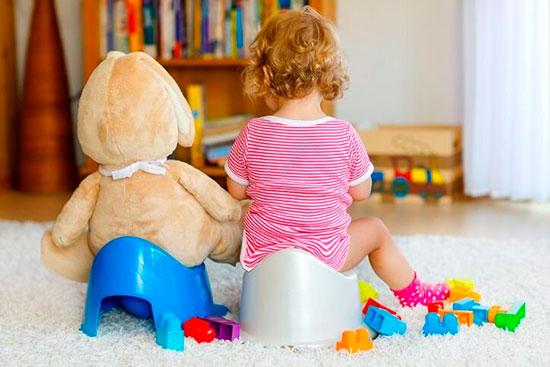 Ребенок и плюшевый мишка сидят на горшке