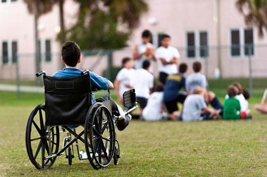 Инвалидная коляска с сидящим в ней ребенком