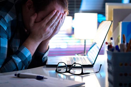 Мужчина в отчаянии закрывает лицо руками сидя перед ноутбуком