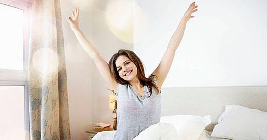 Девушка потягивается в постели после сна