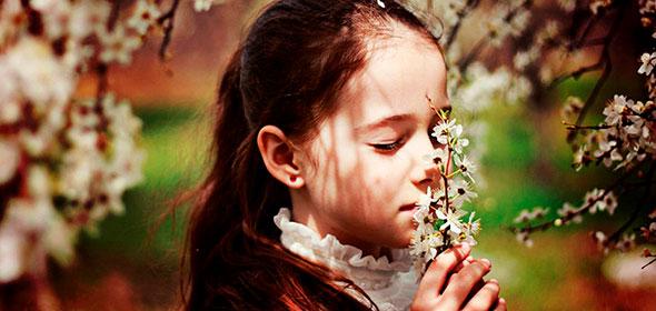 Девочка в поле нюхает цветы