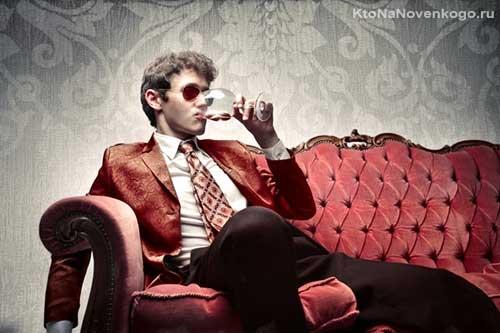 Сибарит сидит на роскошном диване и потягивает вино