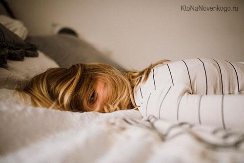 Девушка лежит на кровати не двигаясь